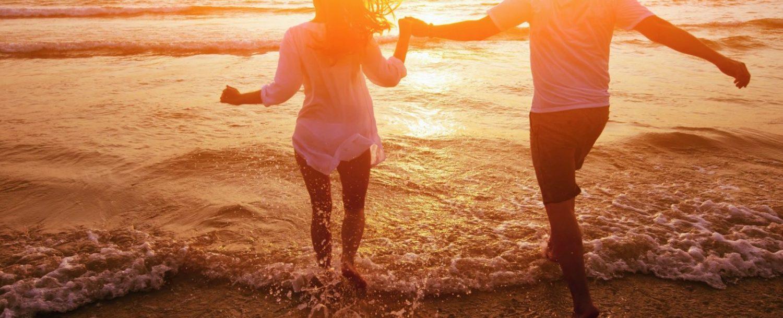 couple running toward ocean at sunset