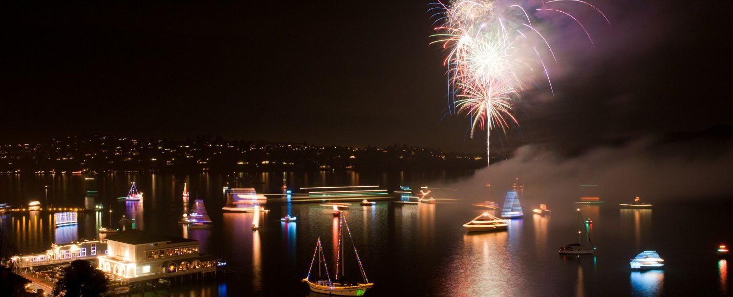 Boats with lights on them and fireworks in the sky