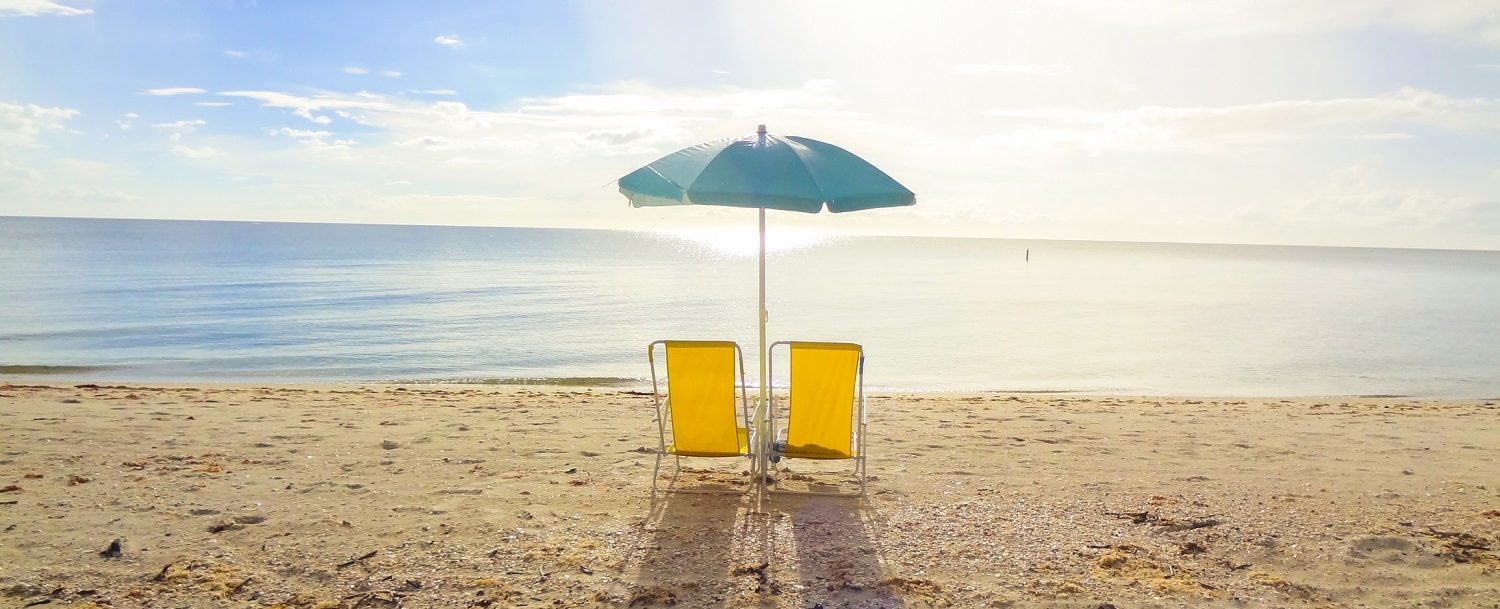 two yellow beach chairs and blue umbrella on the beach