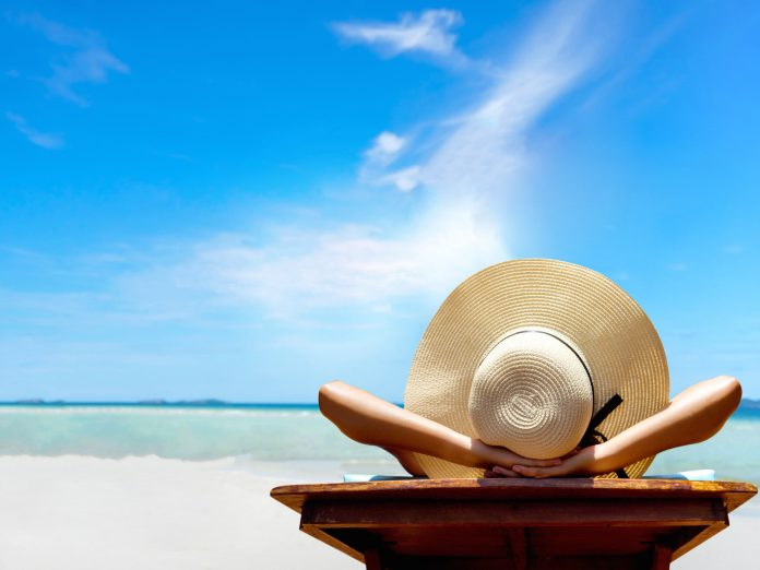 Woman relaxing on the beach with a large hat