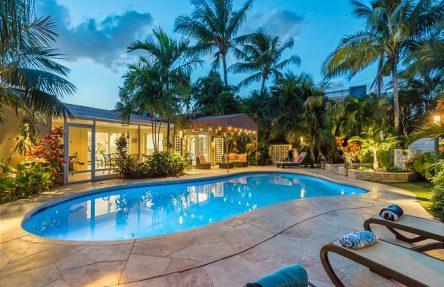 Backyard of rental with glowing pool after sunset, palm trees