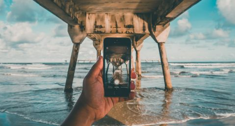 Person taking photo at the beach, one of the most Instagrammable places in Fort Lauderdale