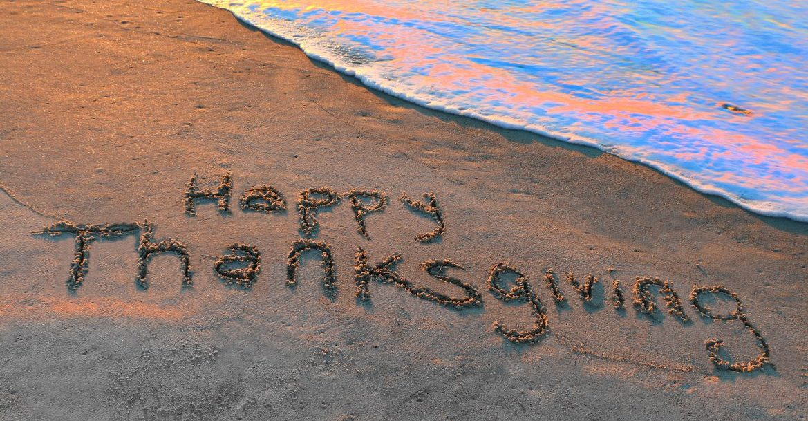 happy thanksgiving in the sand with ocean water rising